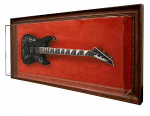 """These are the first two in a set of 19 guitar cases we are currently creating for a casino. Showcase built custom acrylic brackets to secure each unique signed guitar, and the frame room then took a vibrant rust-colored velour fabric and hand-wrapped the MDF backing and fit them into a 4"""" wide special-order bronze frame."""
